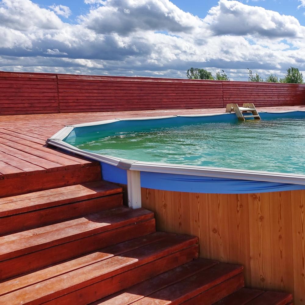 Piscine semi-enterrée avec terrasse en bois