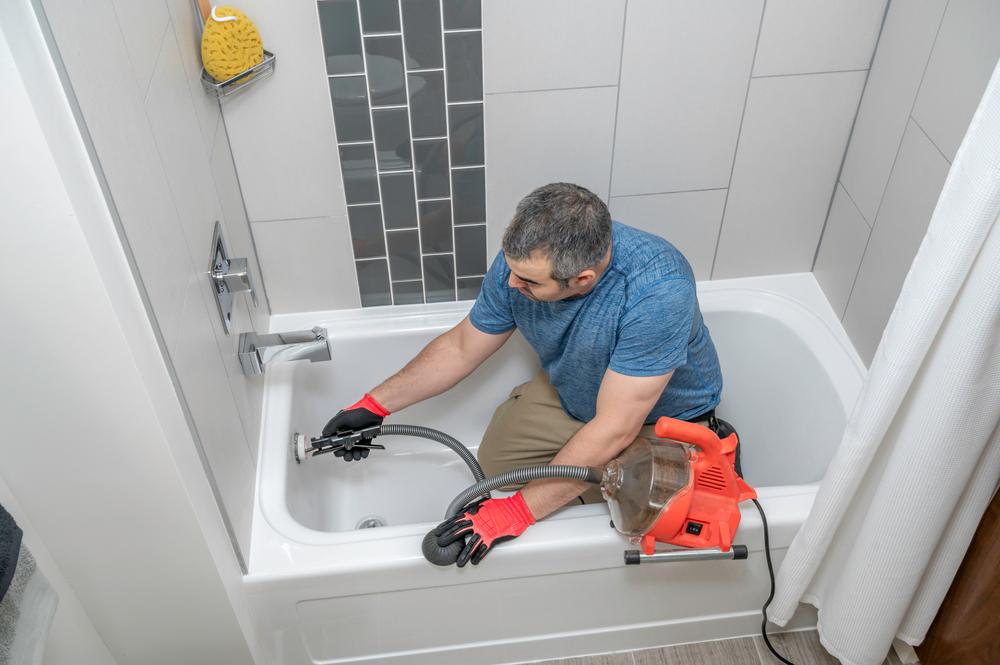 Plombier en train de réparer une baignoire